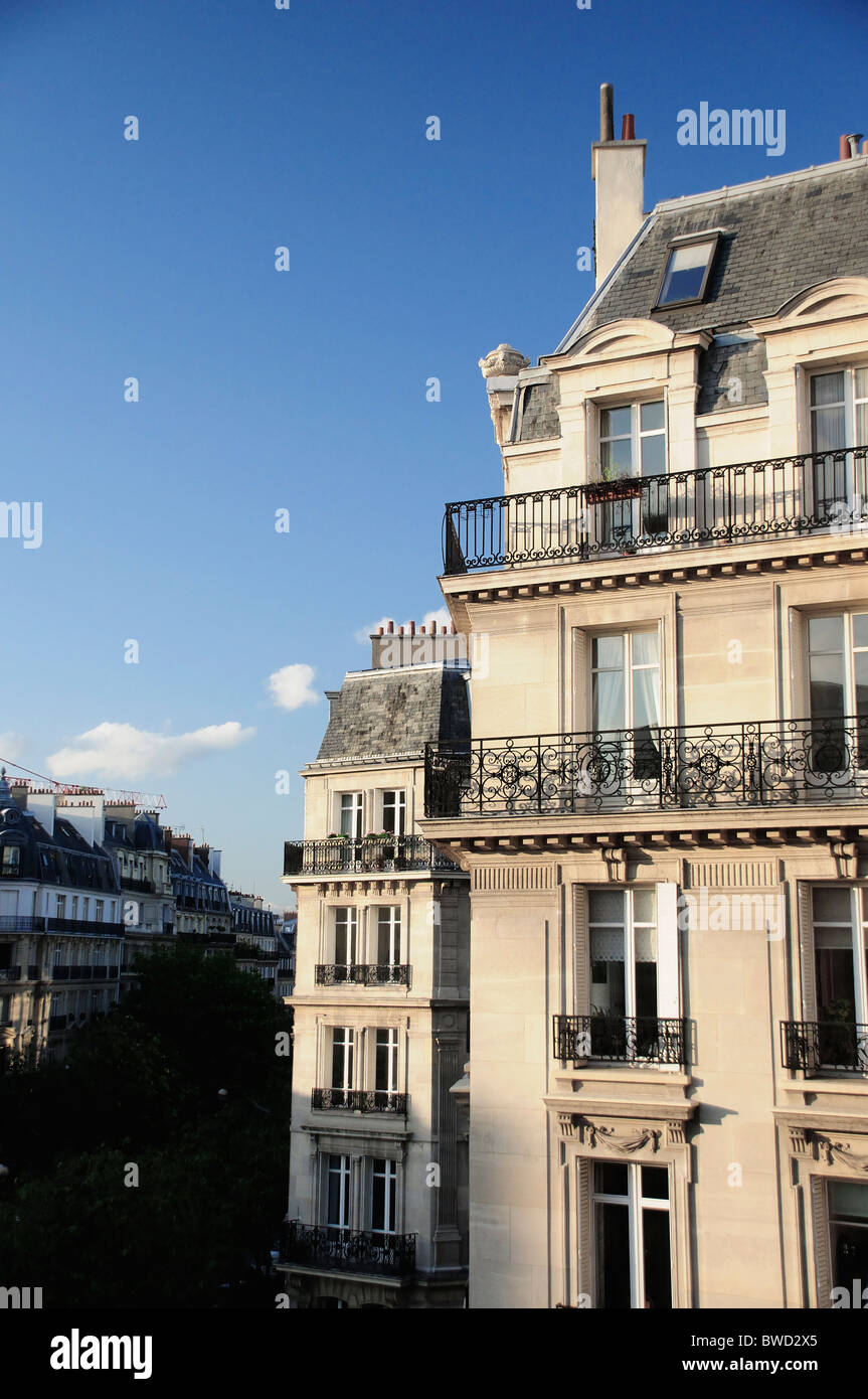 Paris apartment block in afternoon sunlight with clear blue sky - Stock Image