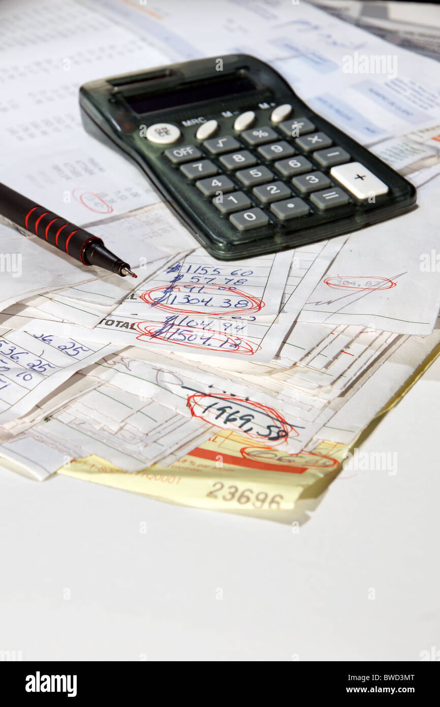 Stack of real bills invoices with calculator and red pen (focus on tip and circled amount) showing debts on white - Stock Image