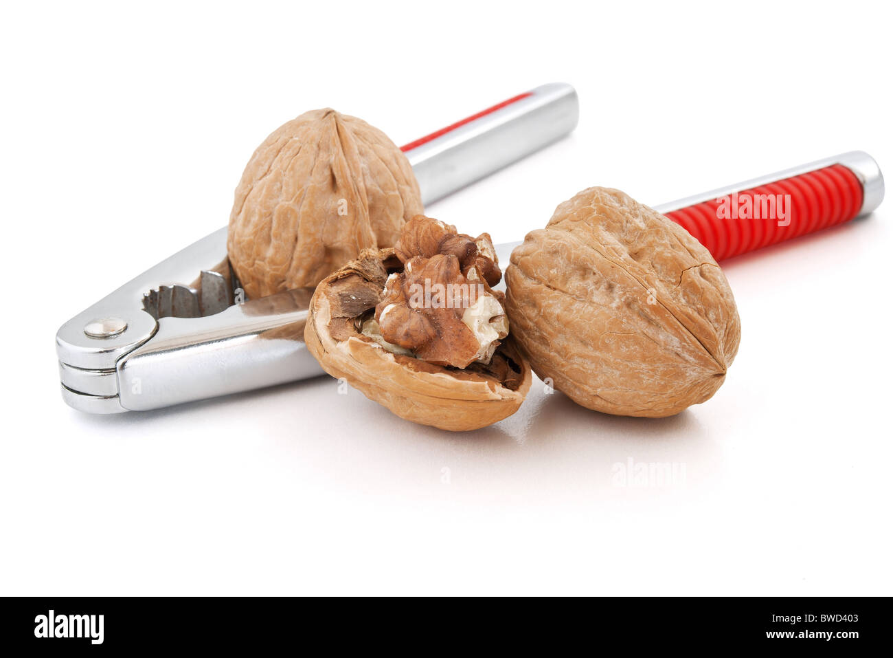 detail of nutcracker with walnuts isolated on white background - Stock Image