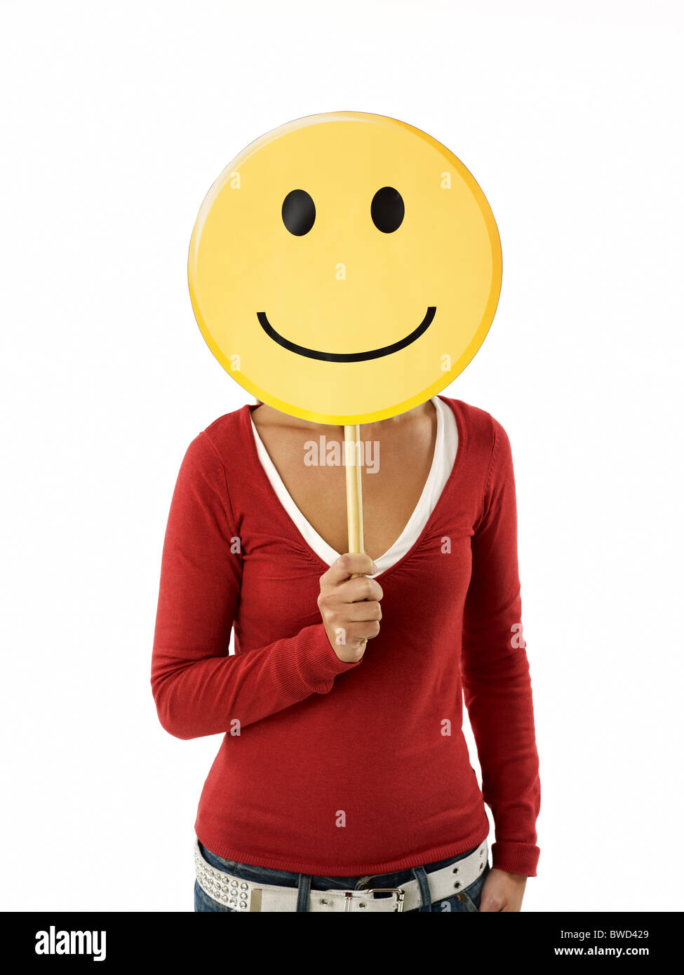 young adult woman holding smiley emoticon on white background. Vertical shape, front view, waist up Stock Photo