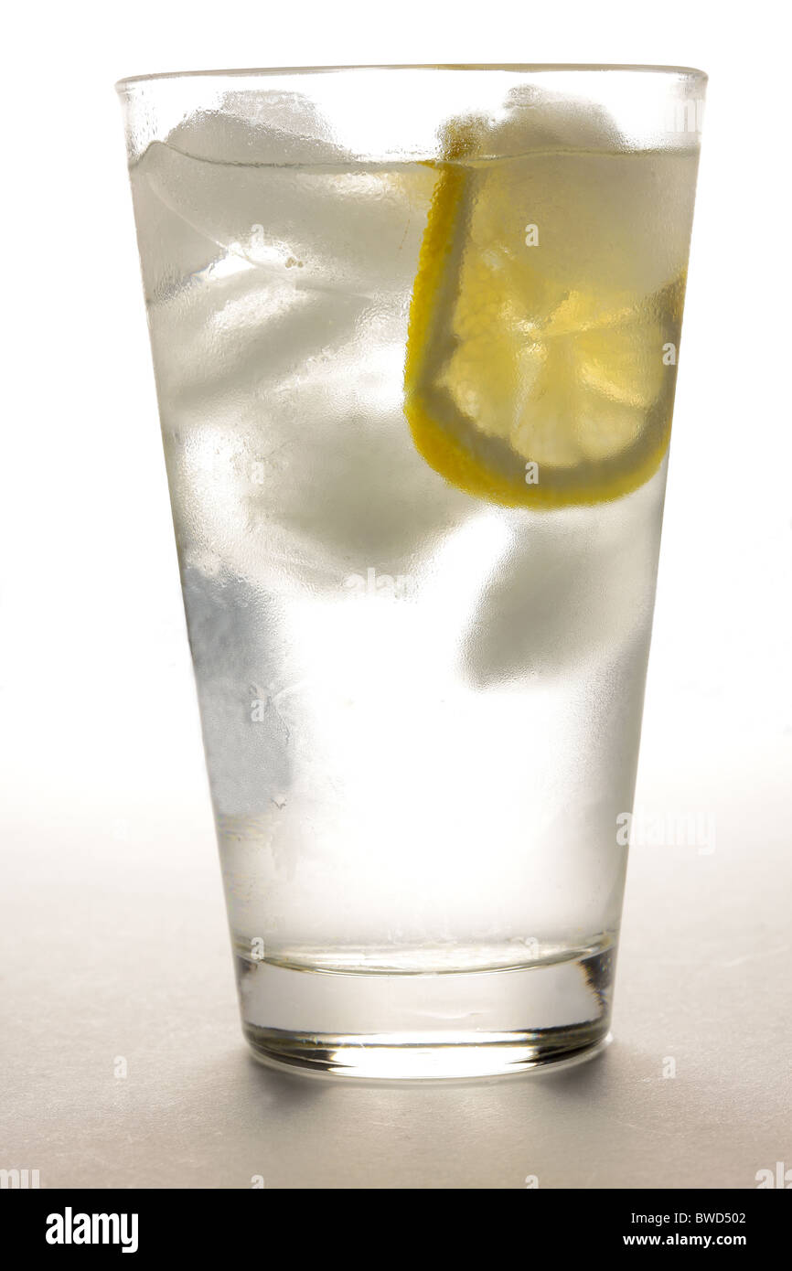 Glass of water with ice and slice of lemon - Stock Image