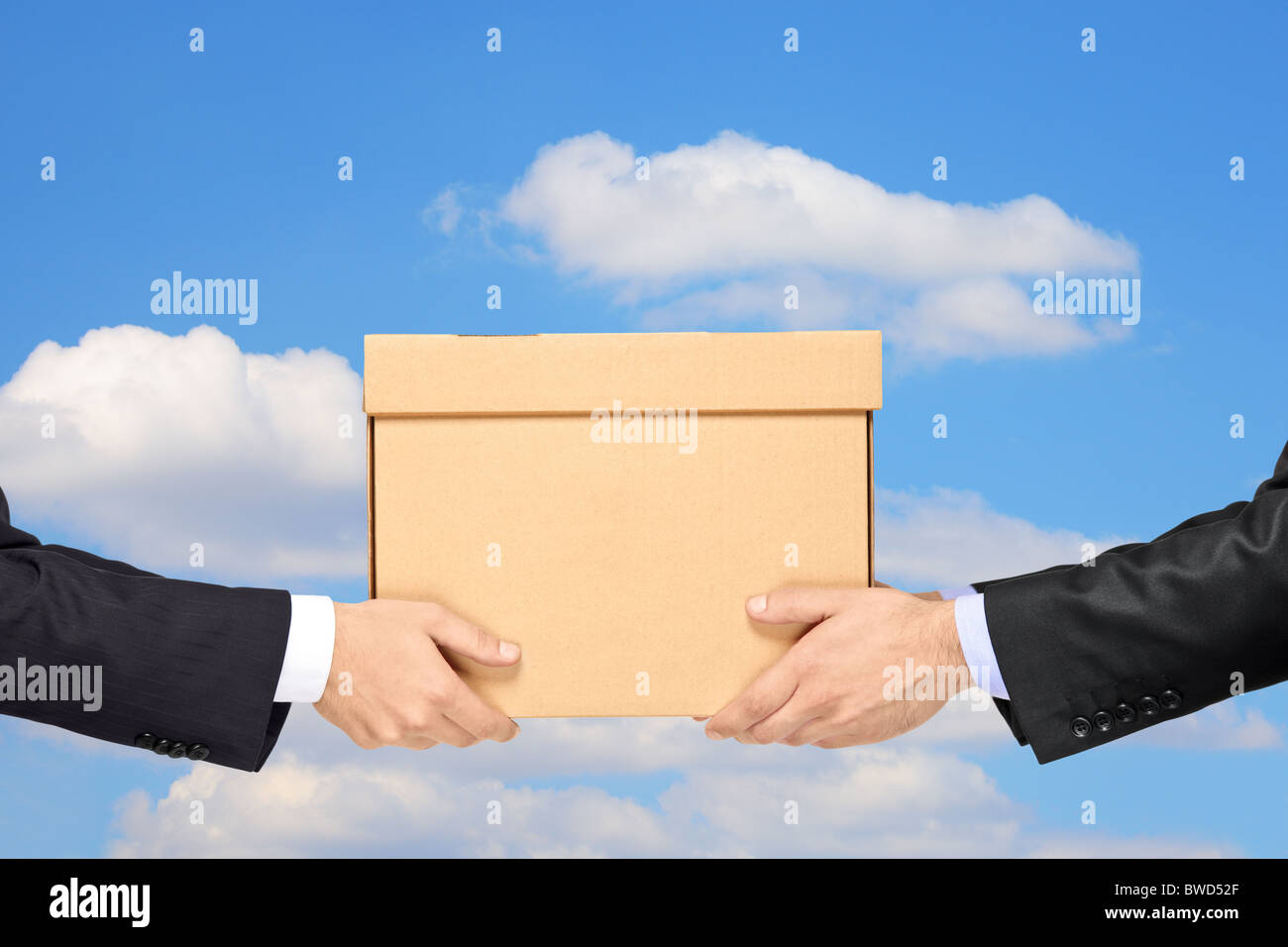 A businessman delivering a package to a man isolated on blue sky - Stock Image