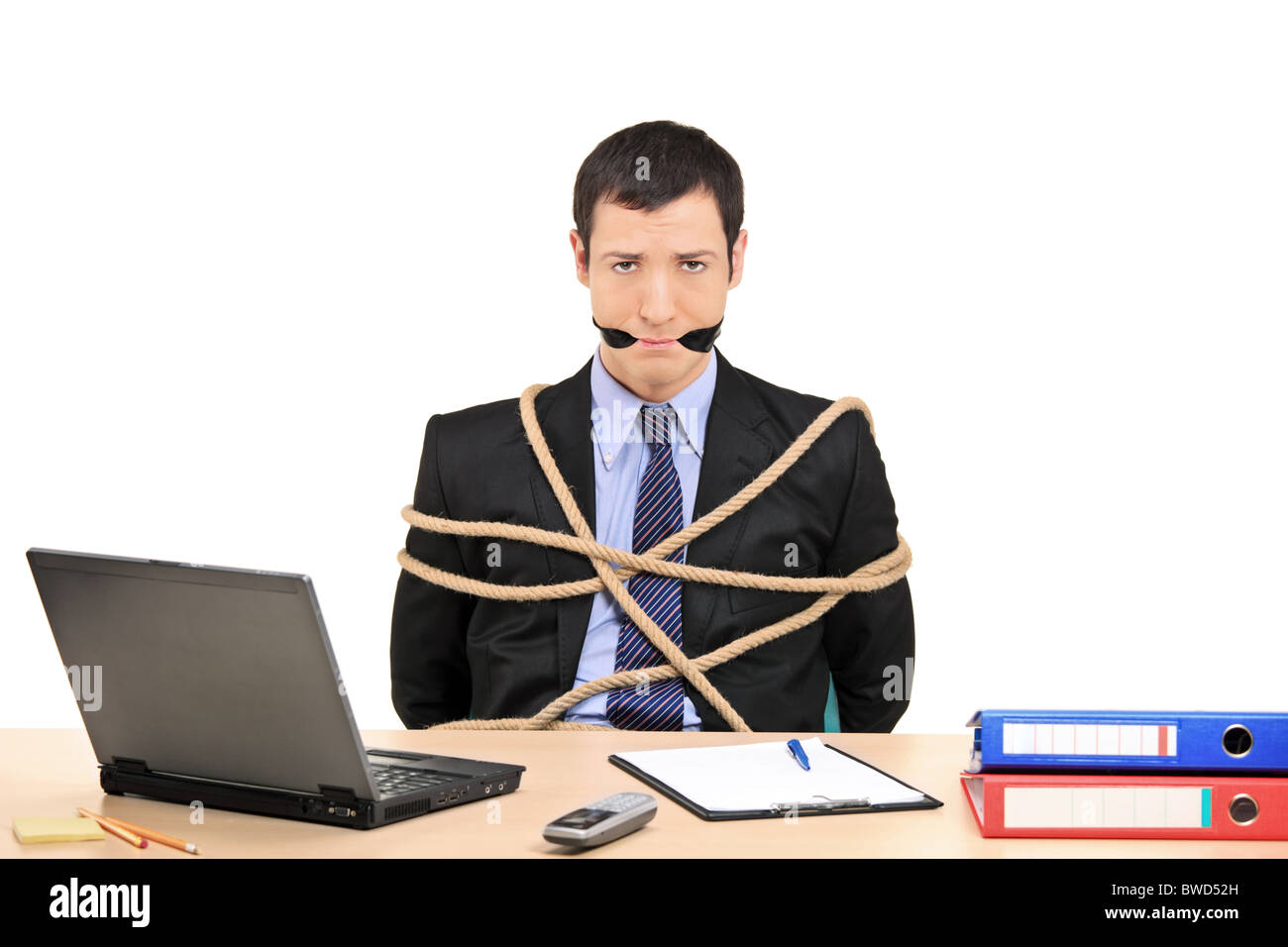 A businessman tied up with rope and gagged with band in the office Stock Photo