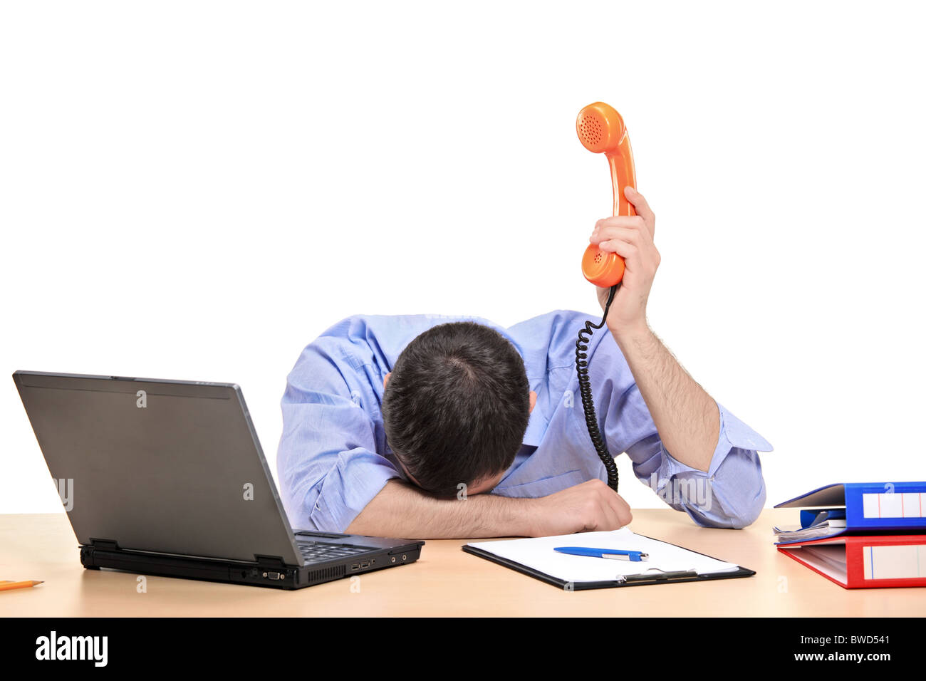 Exhausted businessman holding a telephone tube in his office - Stock Image