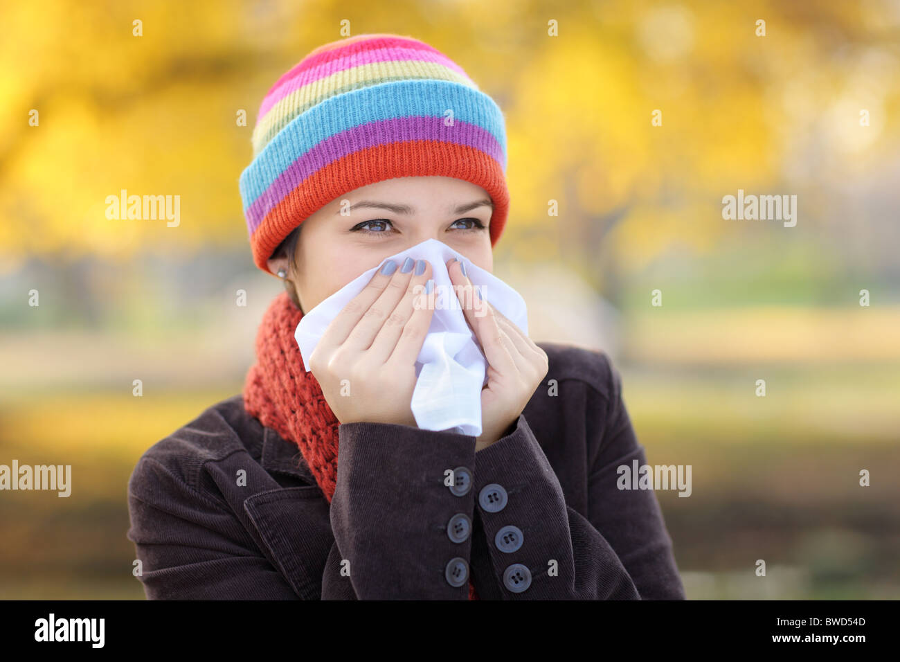 Young woman with tissue having flu or allergy - Stock Image
