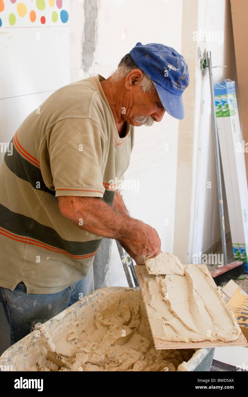 skilled Tiler at work - Stock Image