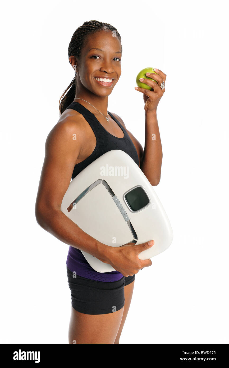 Young African American woman holding weight scale and apple isolated over white background - Stock Image