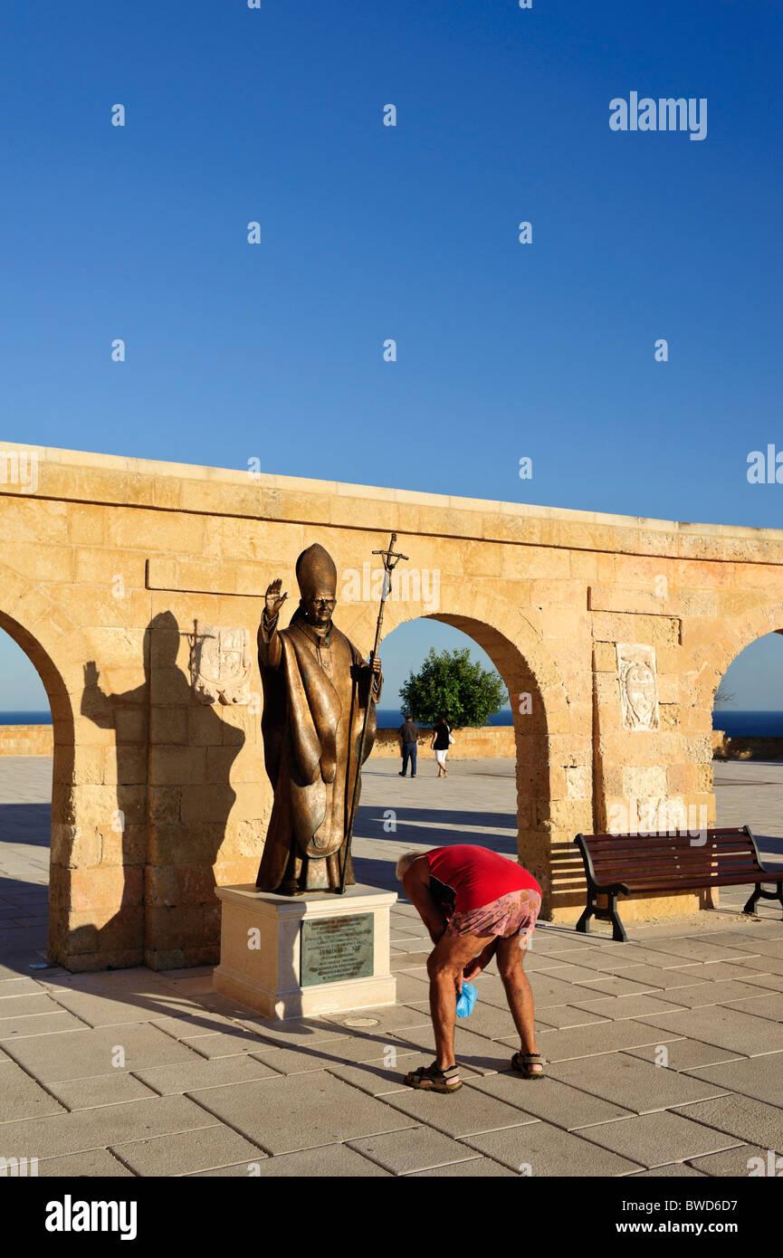 A man bends over in front of a statue of Pope Benedict XVI, Chiesa di Santa Maria di Leuca, Puglia, Italy - Stock Image