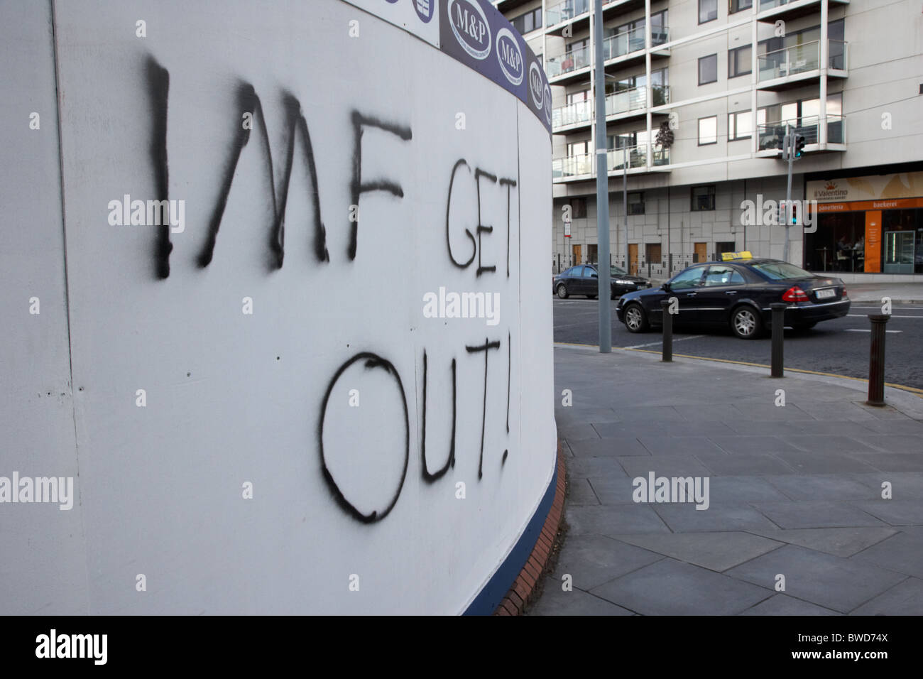 Dublin, Republic of Ireland. Fresh Anti IMF graffiti on a building site wall in an affluent area of Dublin - Stock Image