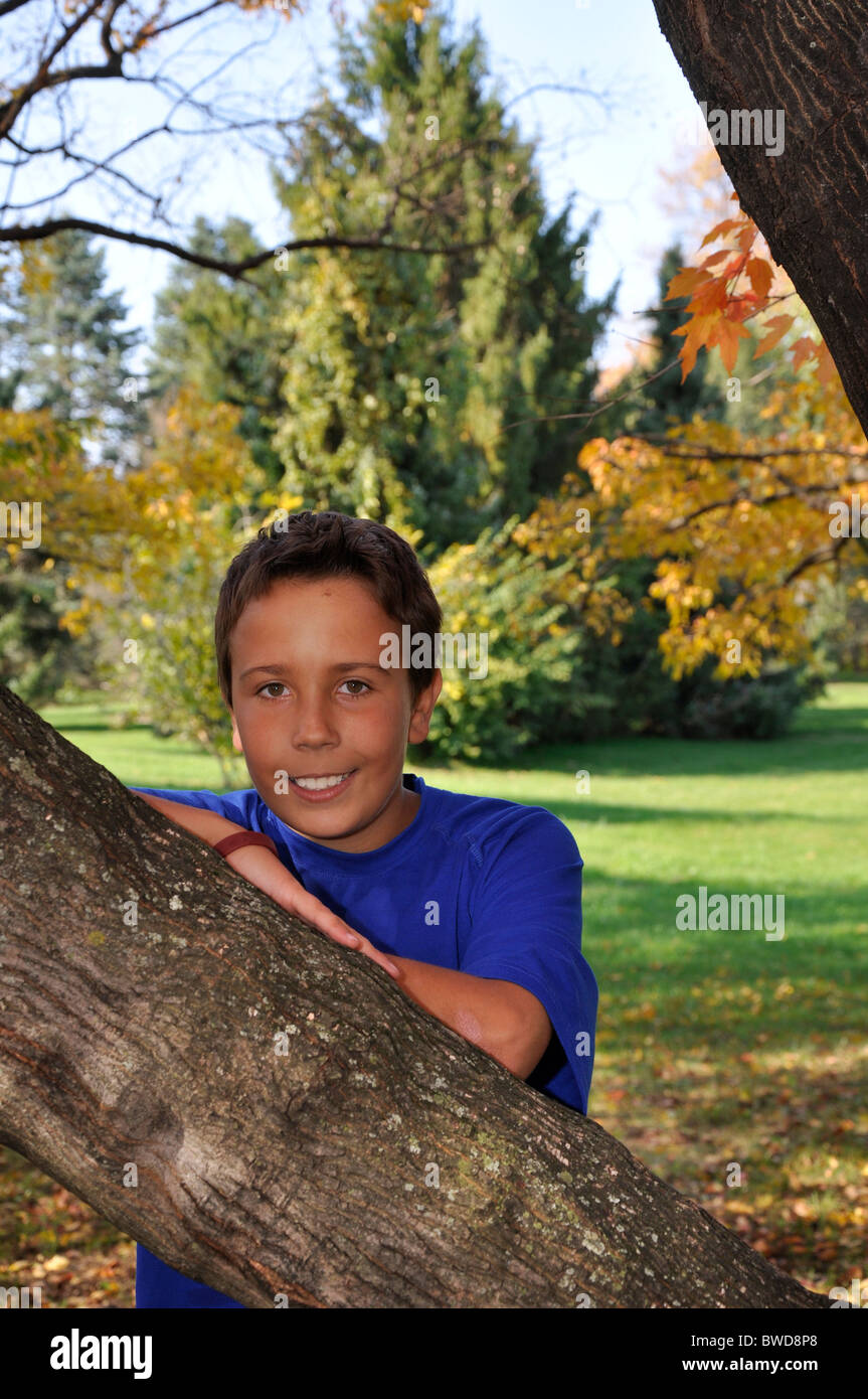 young boy standing under  a tree in autumn.  The boy is smiling and looking at the camera.   He has brown hair. - Stock Image