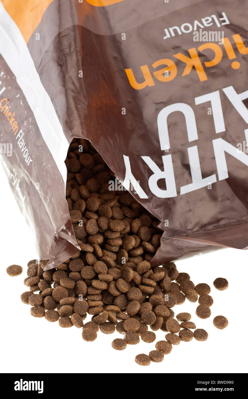 Brown complete dog biscuit food spilling from a 15 kg plastic sack - Stock Image