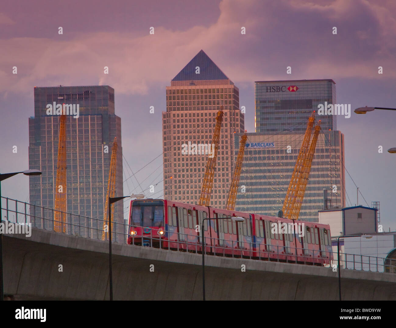 Docklands Light Railway train with Canary Wharf and the towers of the O2 centre behind - Stock Image