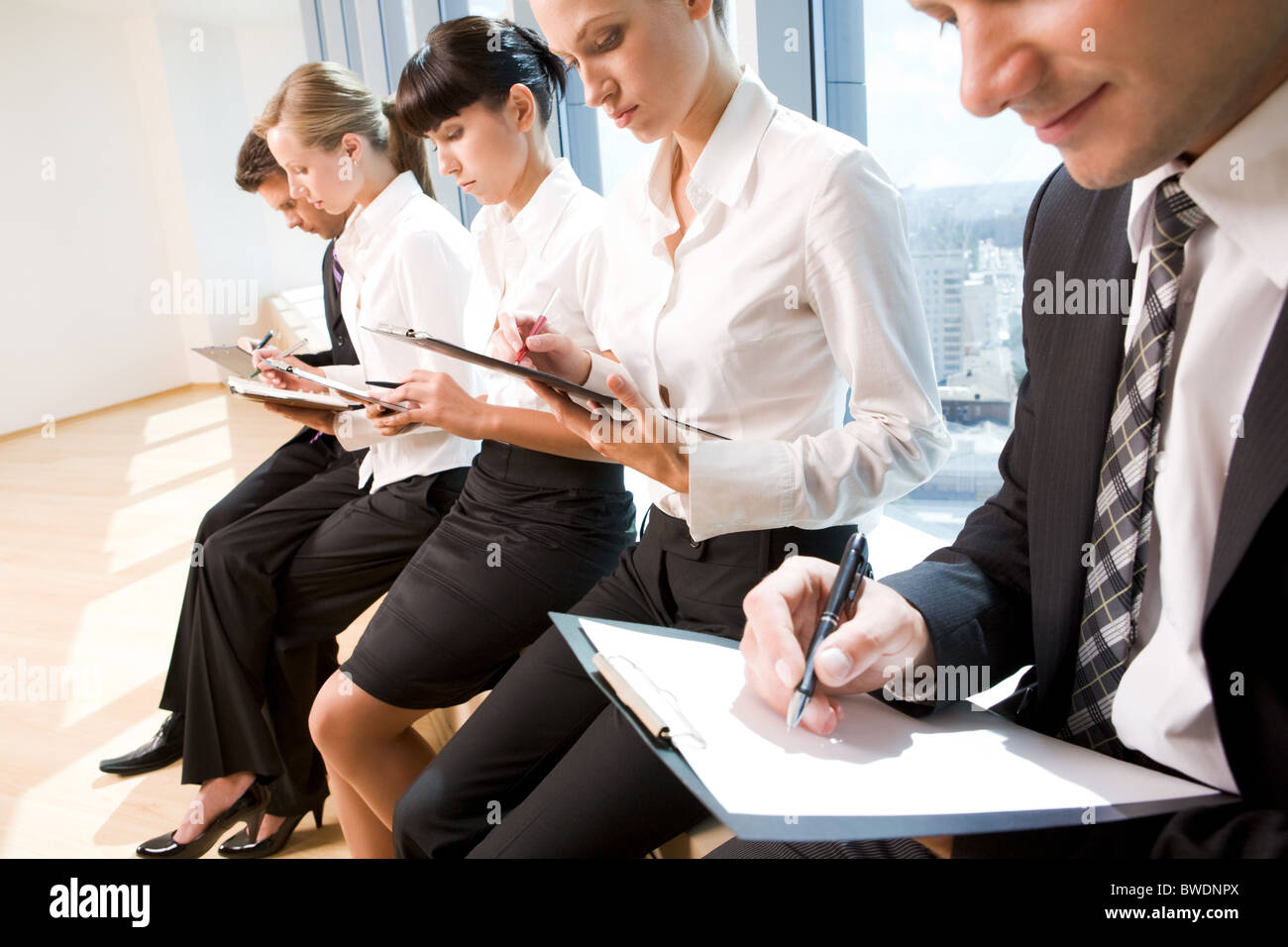 Image of row of business people writing on papers at seminar - Stock Image