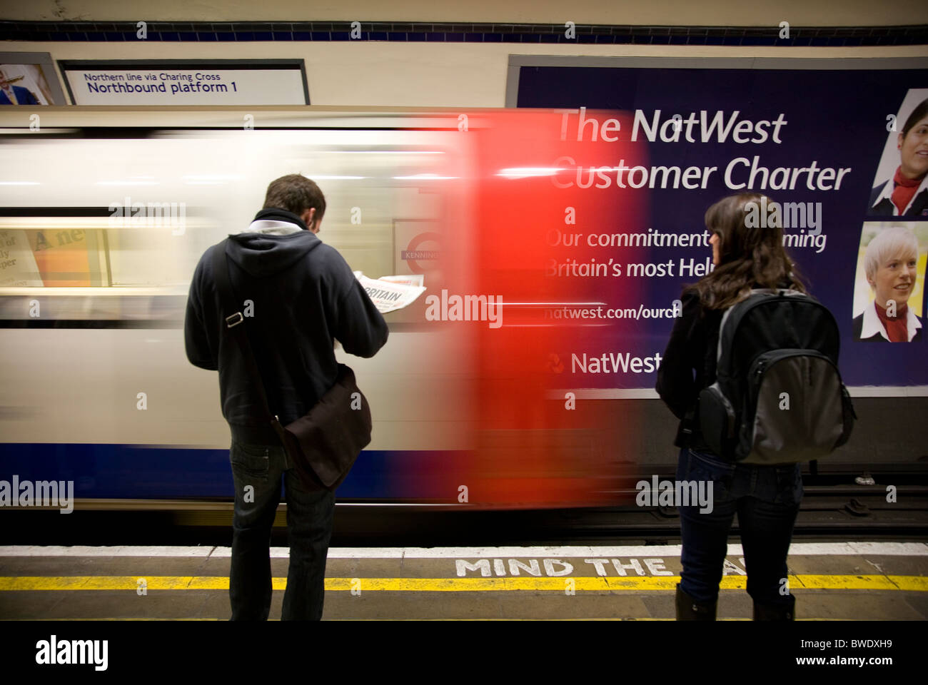 People waiting in front of moving tube at Kennington Station - Stock Image