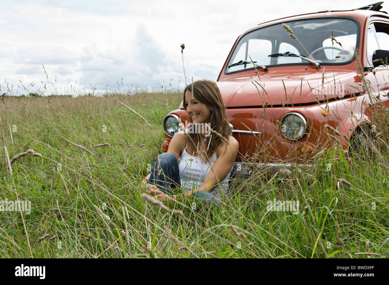 Relaxed female by car in countryside - Stock Image