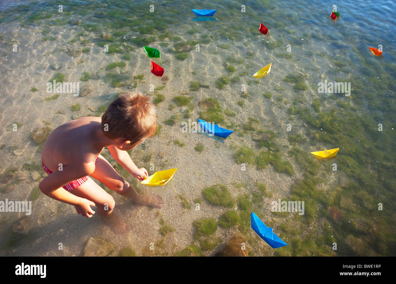 Boy floating paper boats at the beach - Stock Image