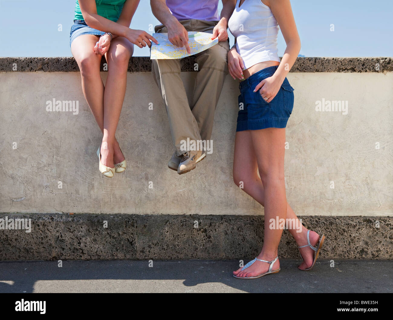 Young people looking at map - Stock Image