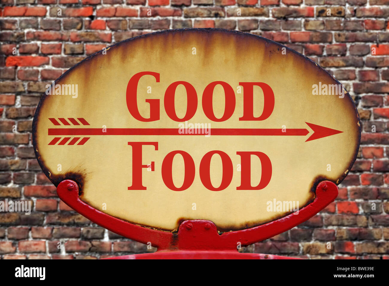 A rusty old retro arrow sign with the text Good Food - Stock Image