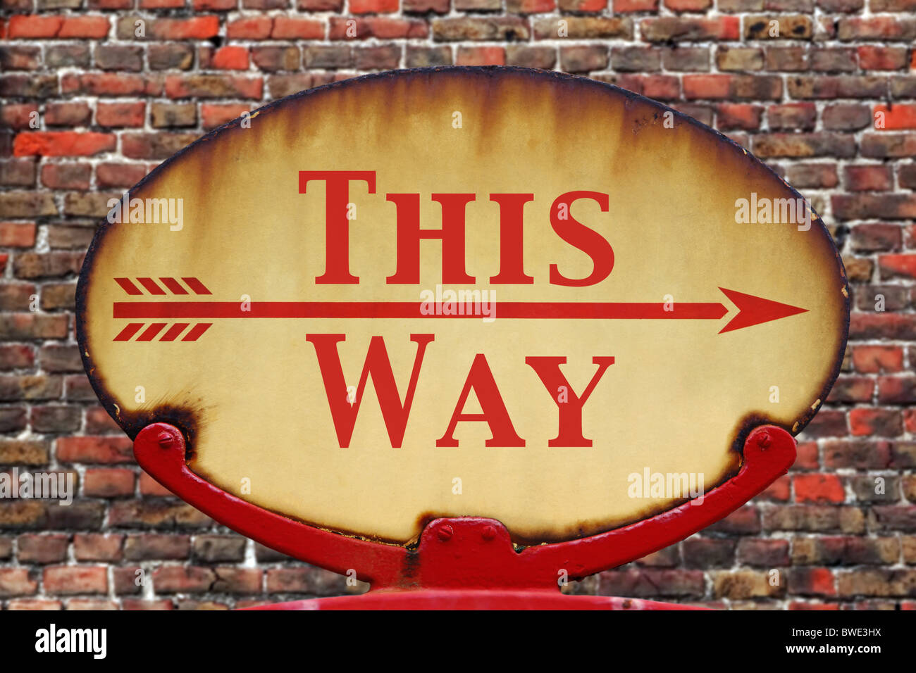 A rusty old retro arrow sign with the text This Way - Stock Image