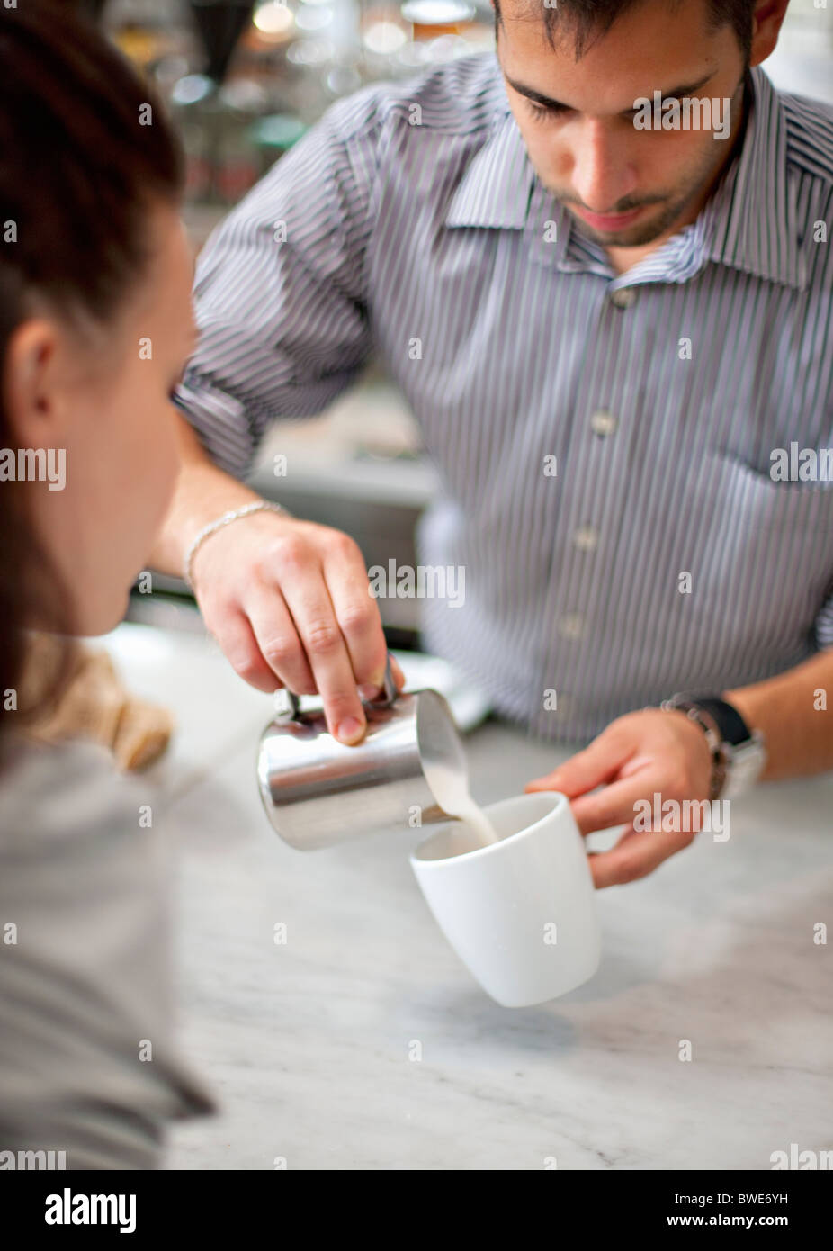 Barkeeper making coffee for woman - Stock Image