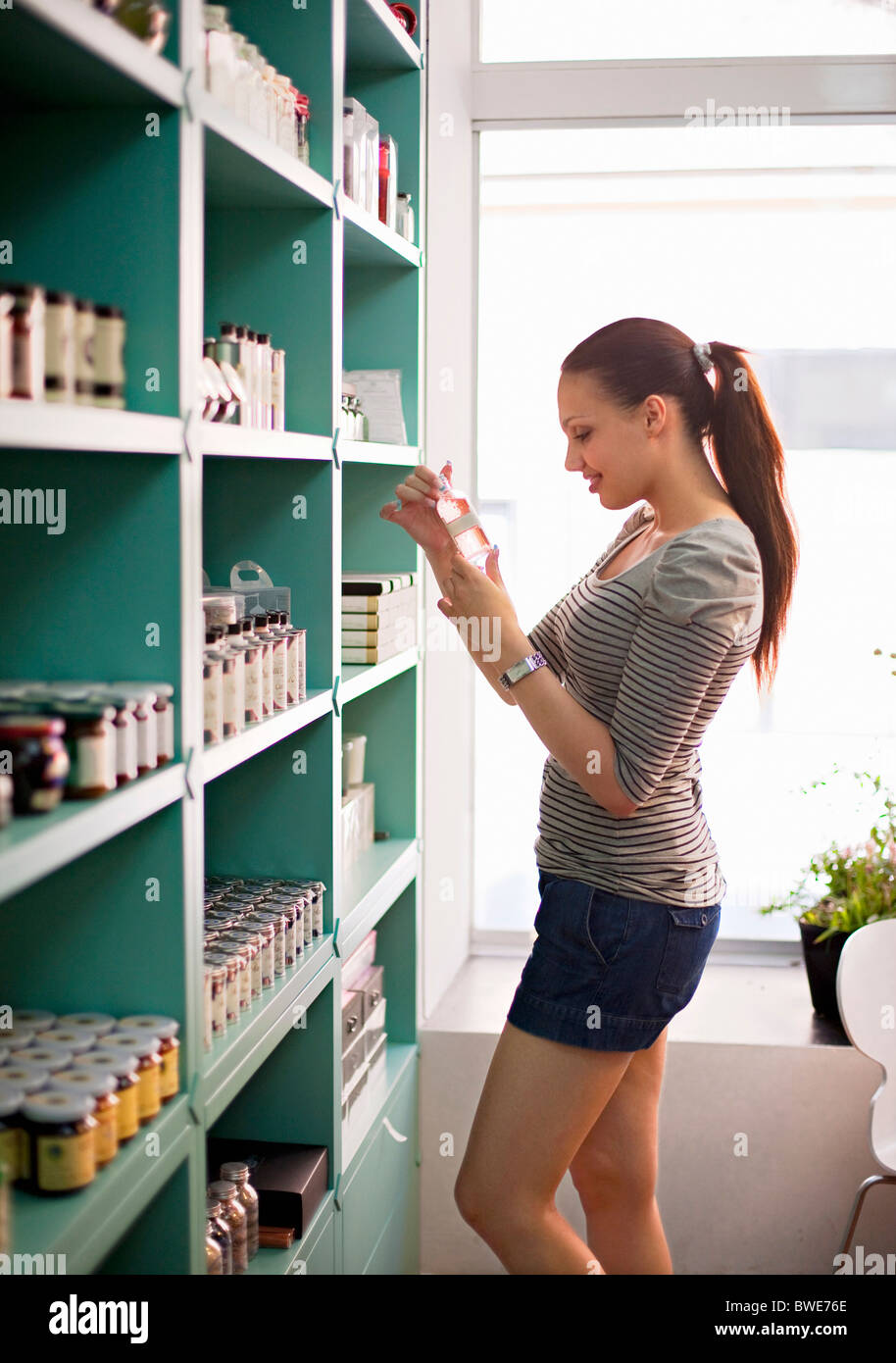 Young woman selecting product - Stock Image