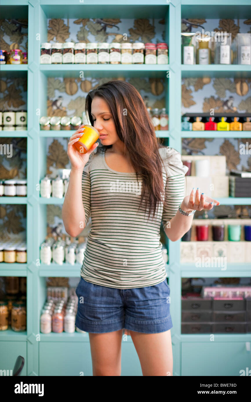 Young woman smelling product - Stock Image