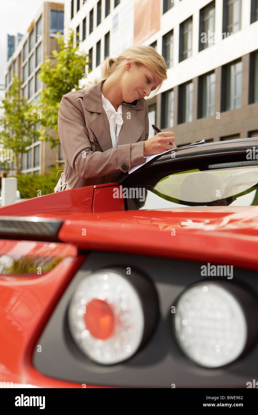Business woman on mobile phone with car - Stock Image