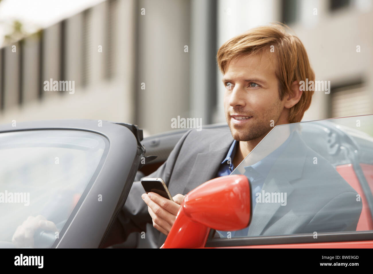 Business man on phone in an electric car Stock Photo