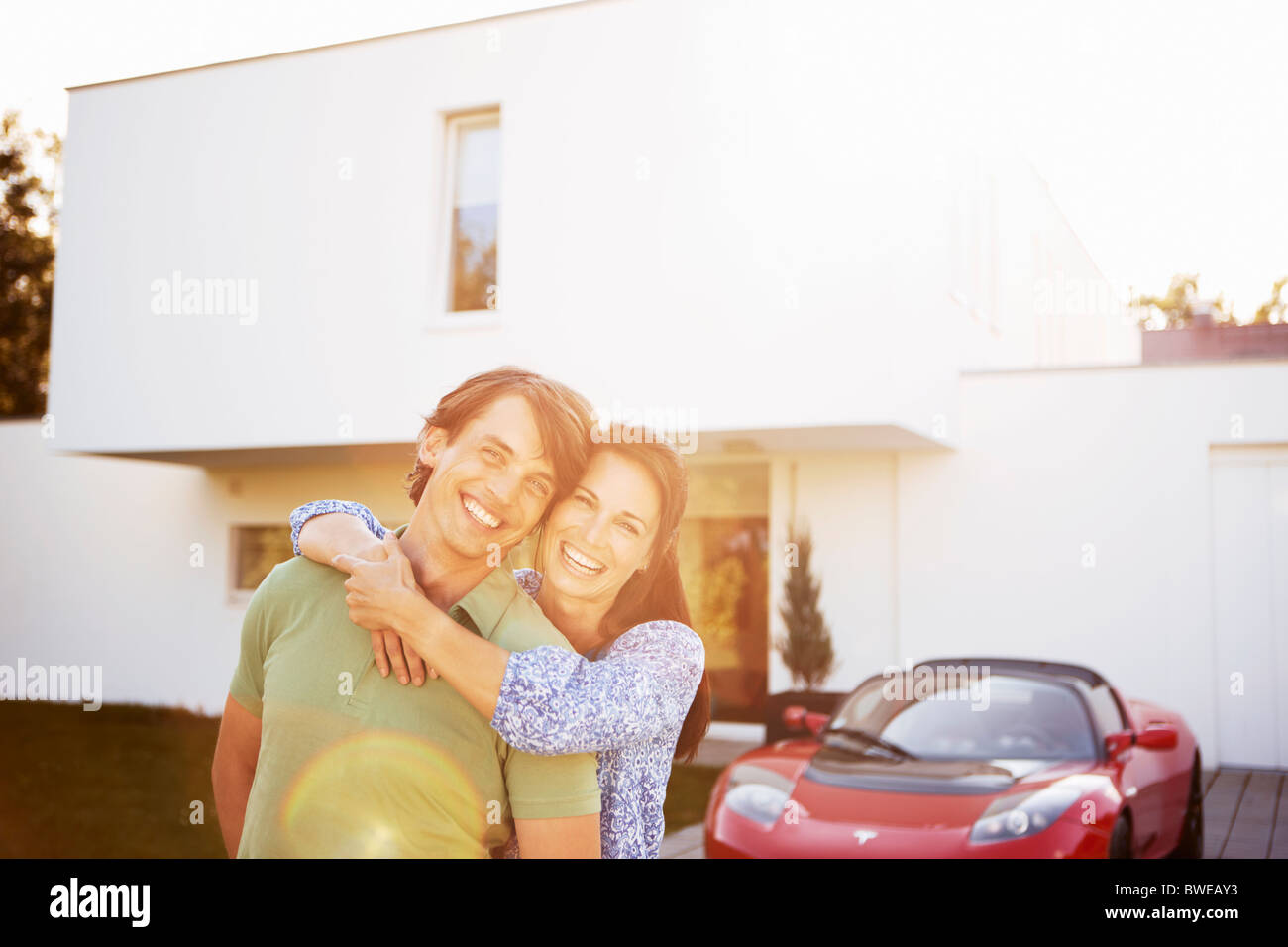 Couple posing in front of house and car Stock Photo