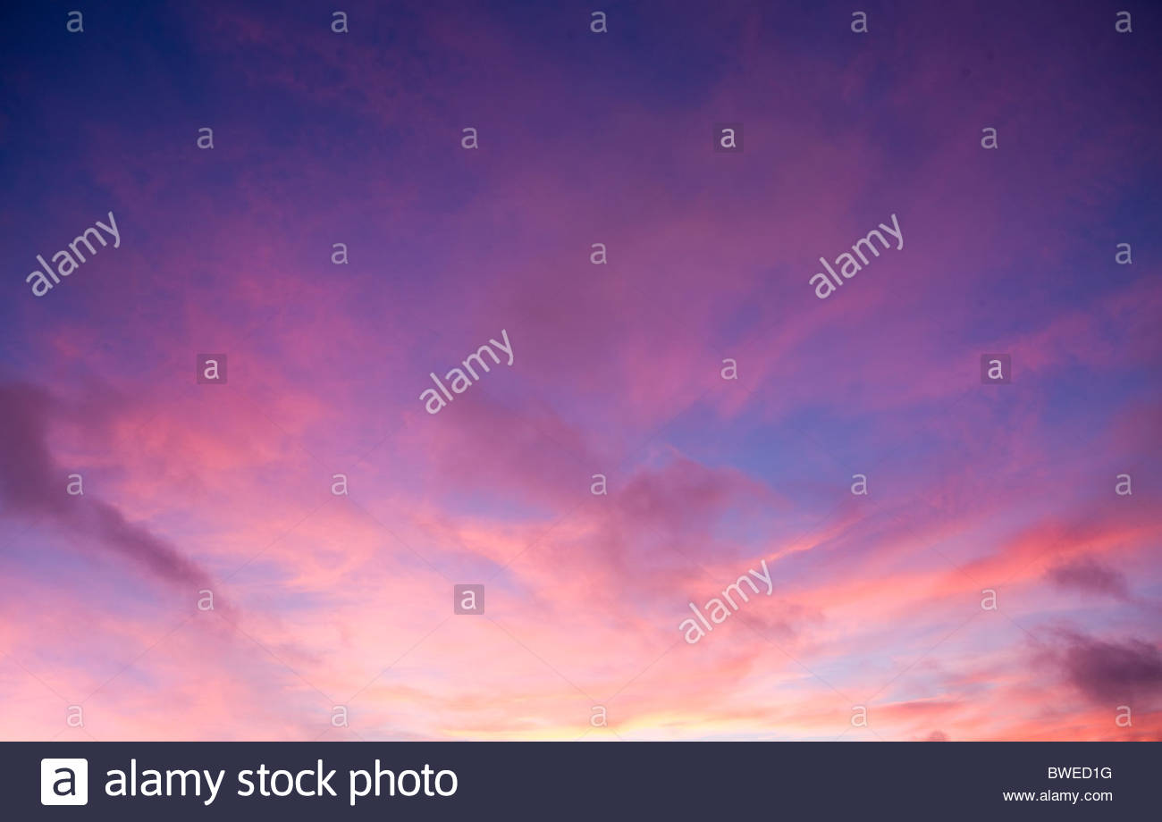 Clouds at sunset in pink and purple sky - Stock Image