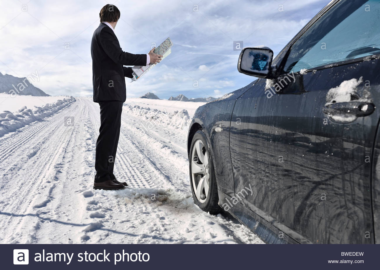 Mid adult businessman standing next to car with road map on winter day - Stock Image