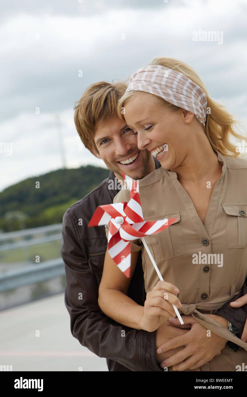 Couple holding handheld windmill - Stock Image