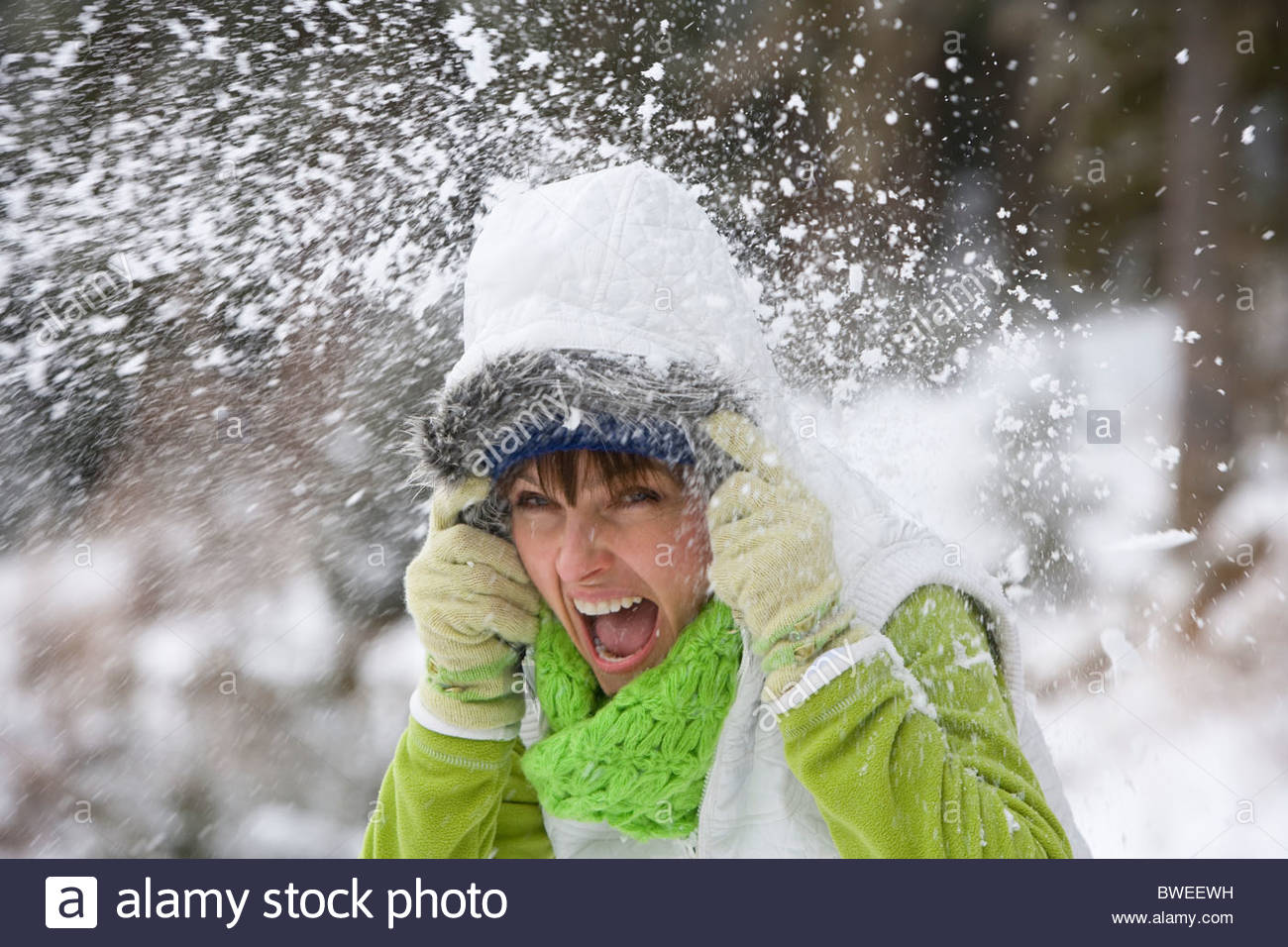 Shouting woman getting hit with snowball - Stock Image