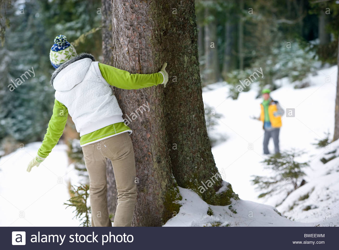 Couple playing hide and seek in woods together Stock Photo