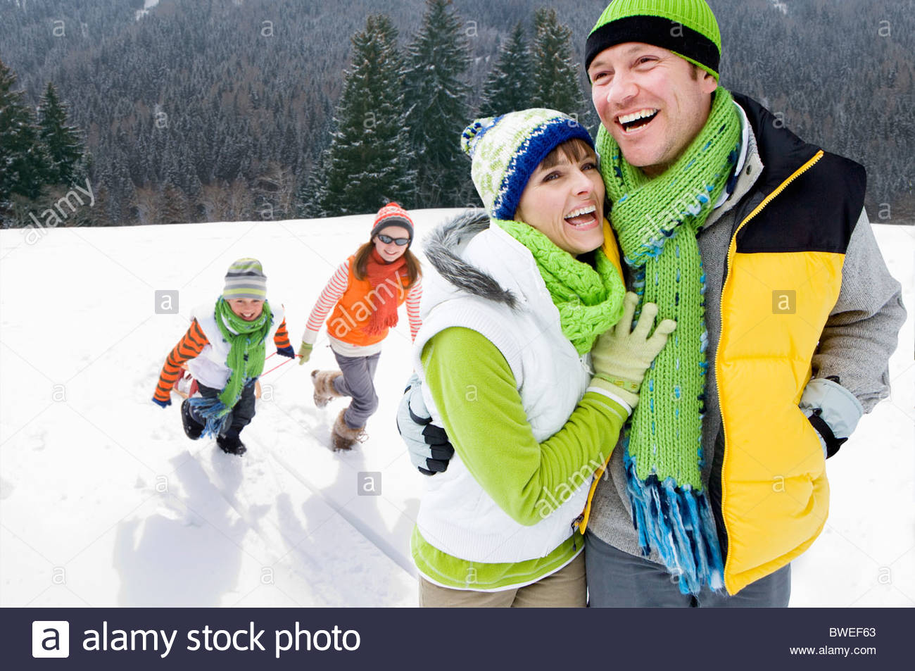 Smiling family walking in snowy woods together - Stock Image