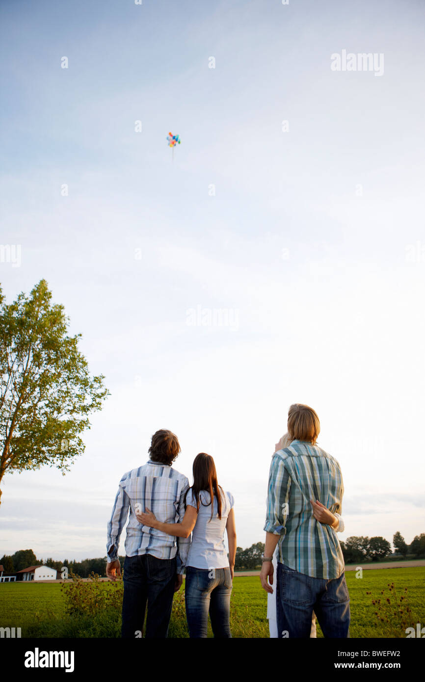 2 couples watching balloons rise in sky - Stock Image