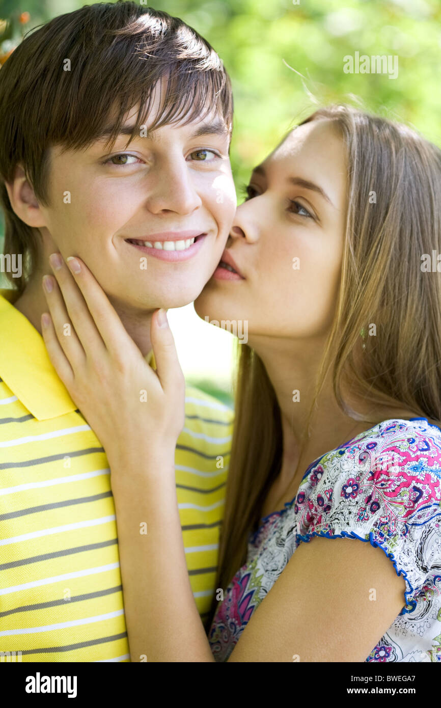 Pretty girl kissing tenderly her boyfriend while he smiling at camera - Stock Image