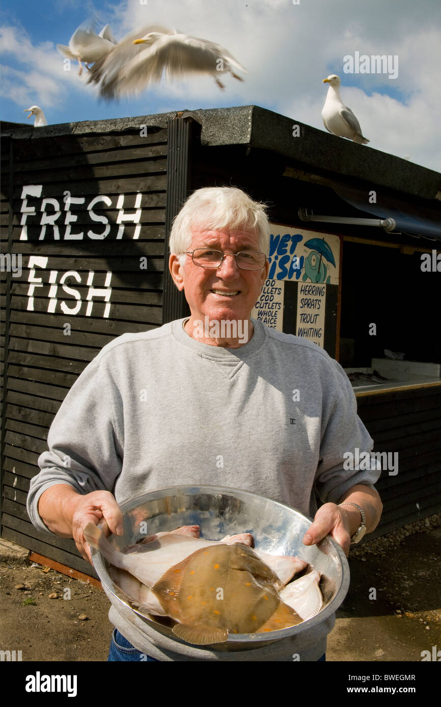 Arthur Read 30 yrs fisherman sells fresh fish at his fish stall in Hastings Old Town excites seagulls with early - Stock Image