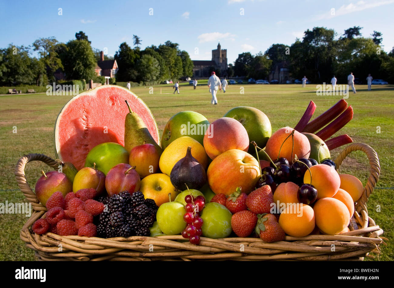Basket of delicious locally grown fresh healthy summer fruits beside Benenden Village Green with cricket match in Stock Photo