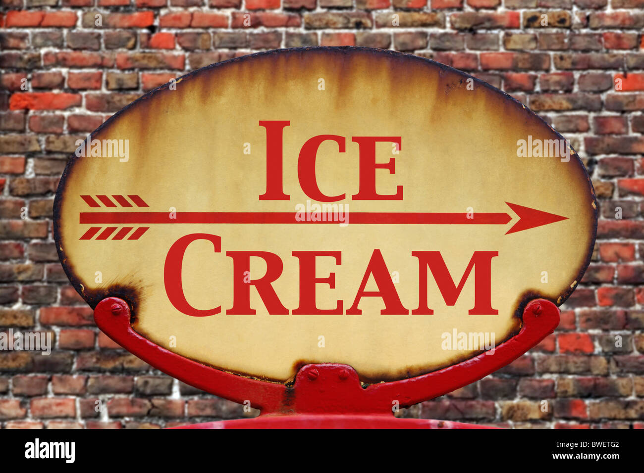 A rusty old retro arrow sign with the text Ice cream - Stock Image