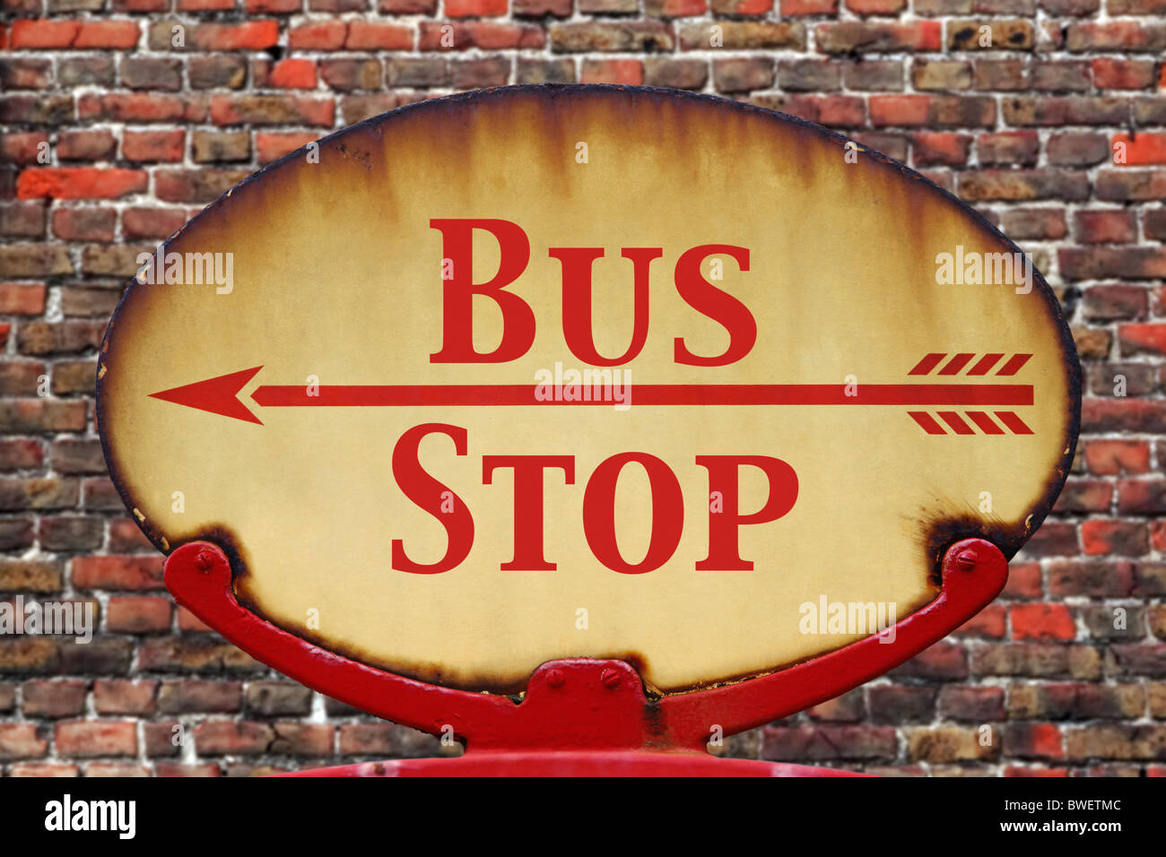 A rusty old retro arrow sign with the text Bus stop - Stock Image