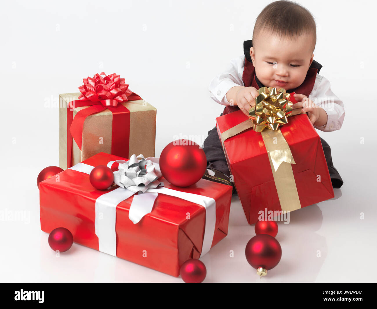 Six month old baby boy opening Christmas presents. Isolated on white background. - Stock Image