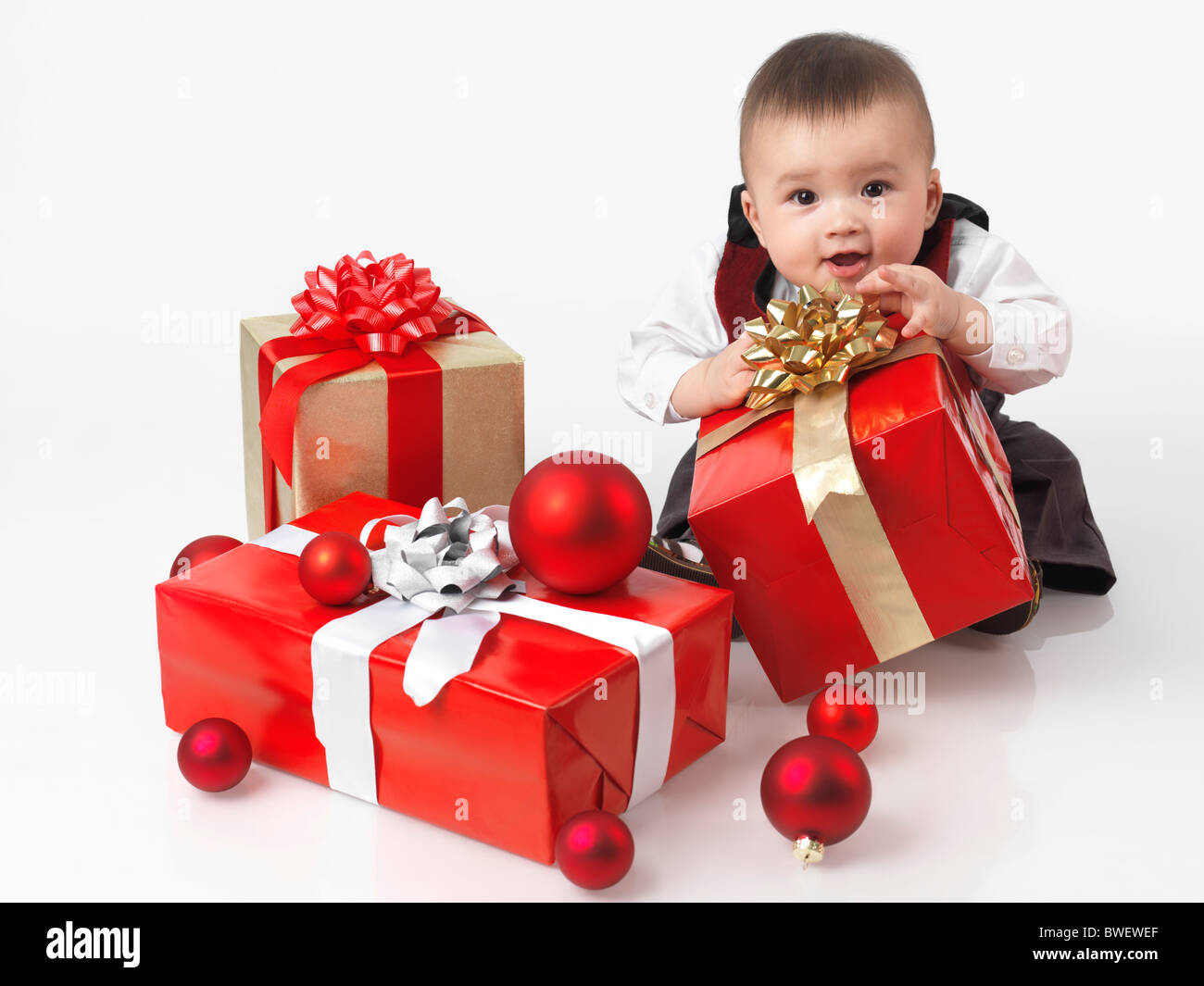Happy six month old baby boy opening Christmas presents. Isolated on white background. - Stock Image