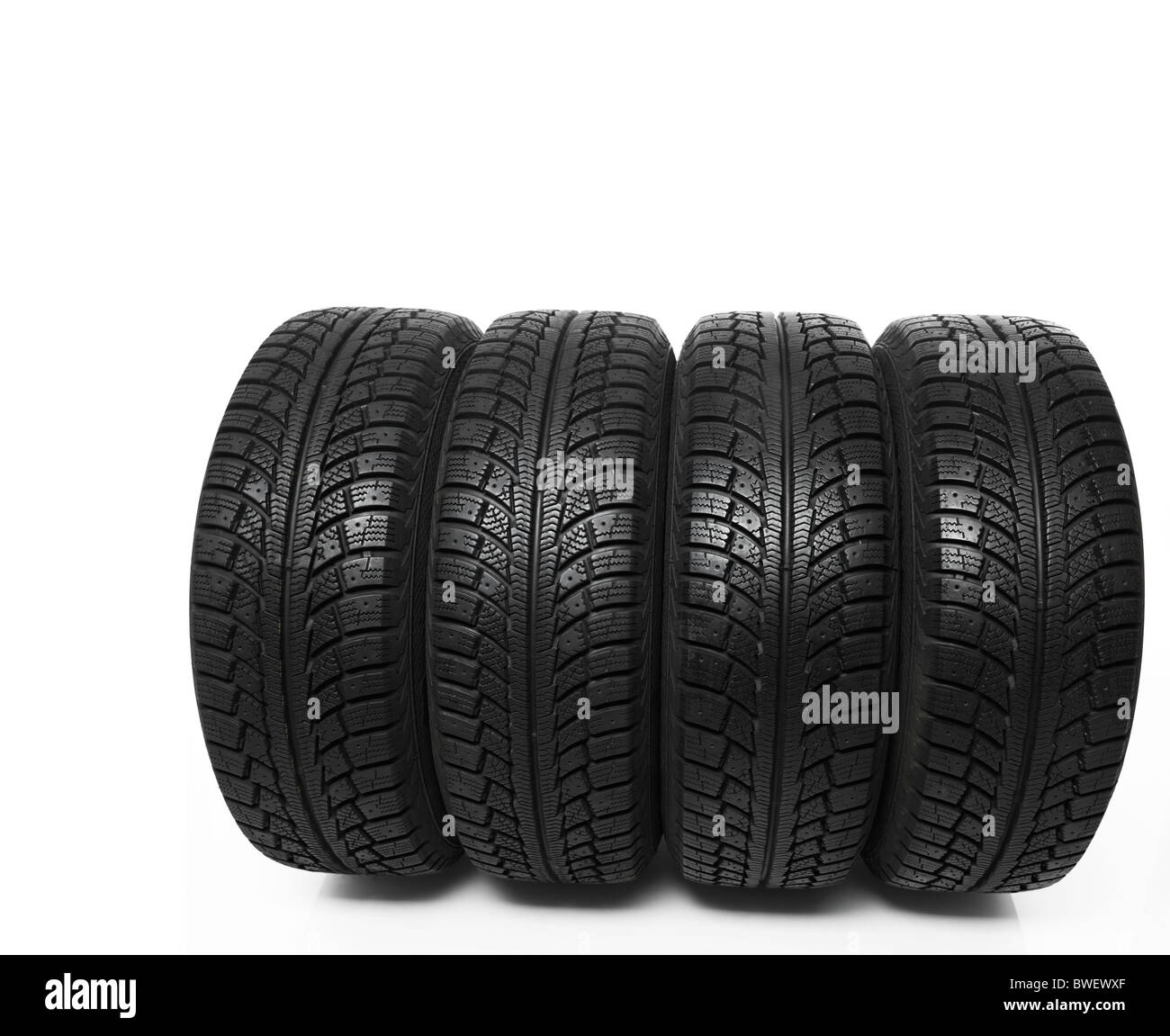 Set of four winter tires isolated on white background - Stock Image