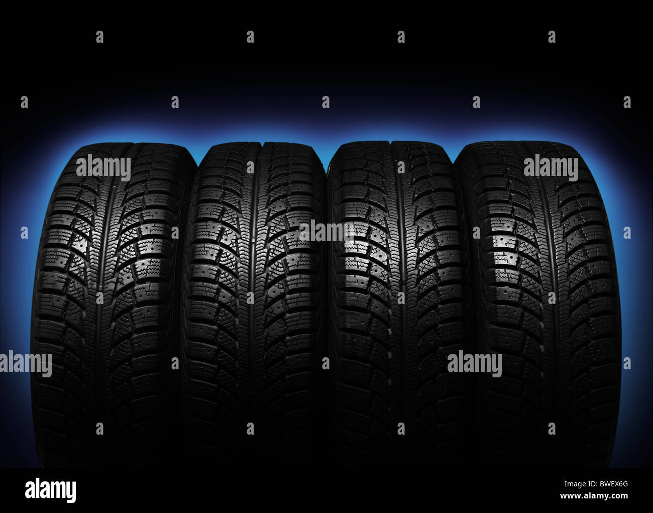 Set of four winter tires isolated on blue black background - Stock Image