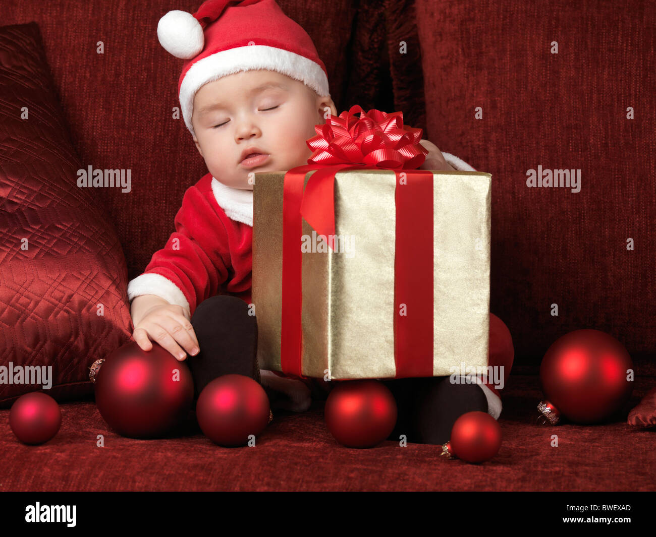 Six month old baby boy in Santa costume sleeping with a Christmas present in his lap - Stock Image