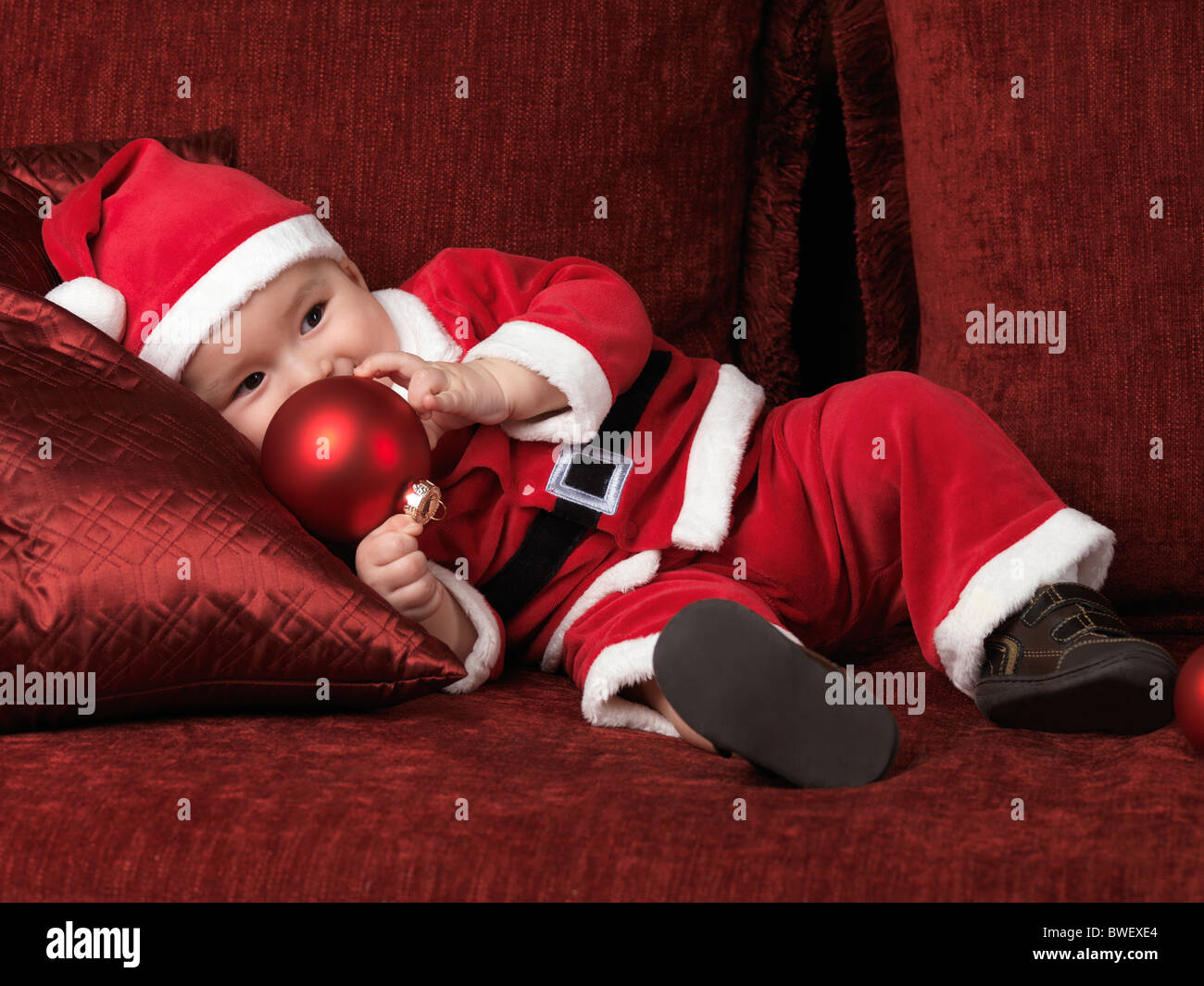 Six month old baby boy in Santa Christmas costume holding a red bauble in his hand - Stock Image