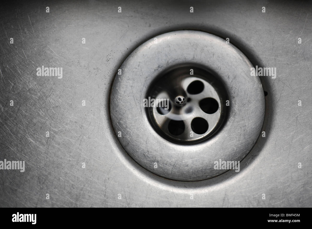 Water disappearing down the plug hole in a sink. - Stock Image