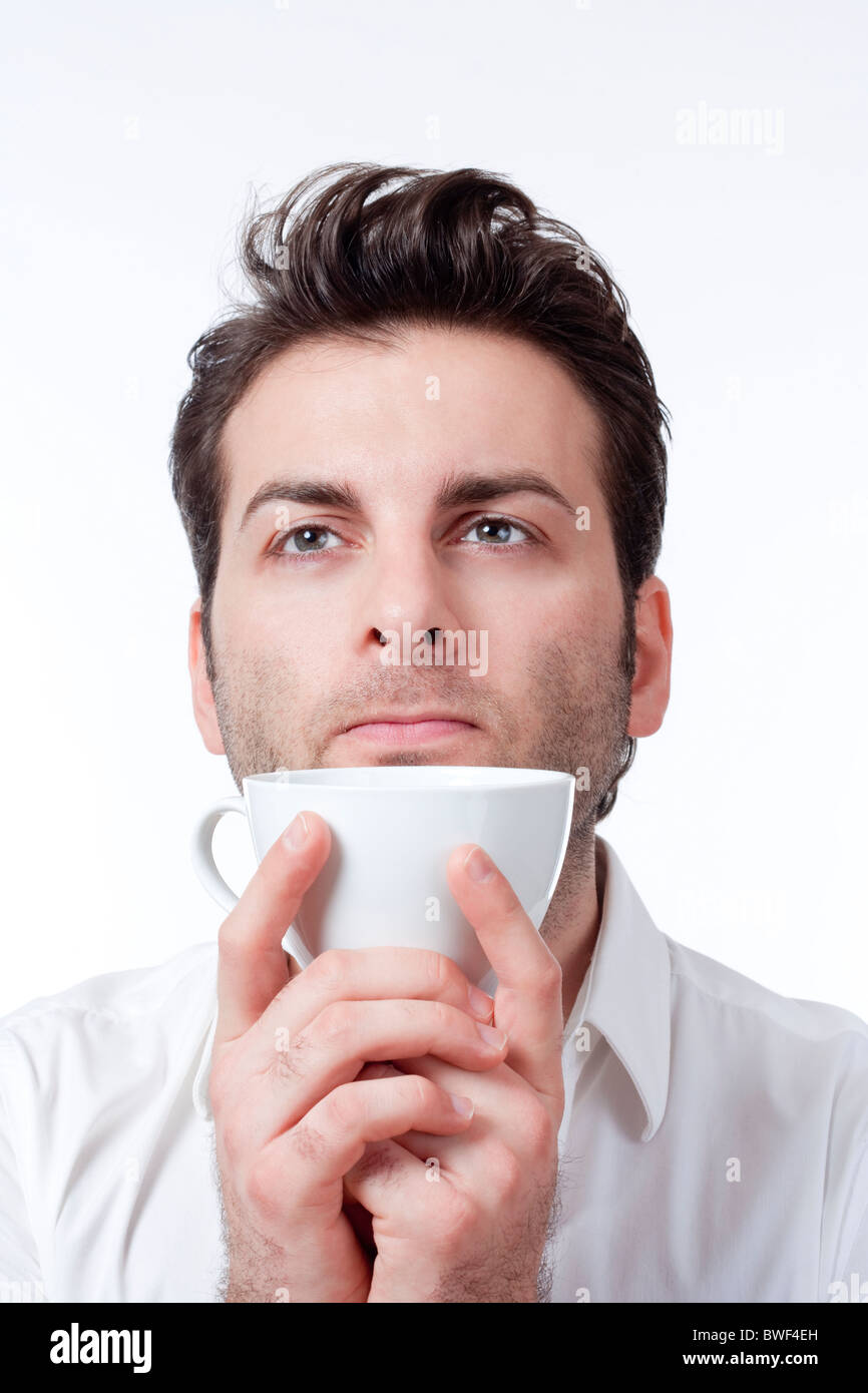 man in shirt holding cup of coffee looking up - isolated on white - Stock Image