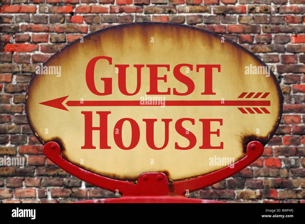 A rusty old retro arrow sign with the text Guest house - Stock Image